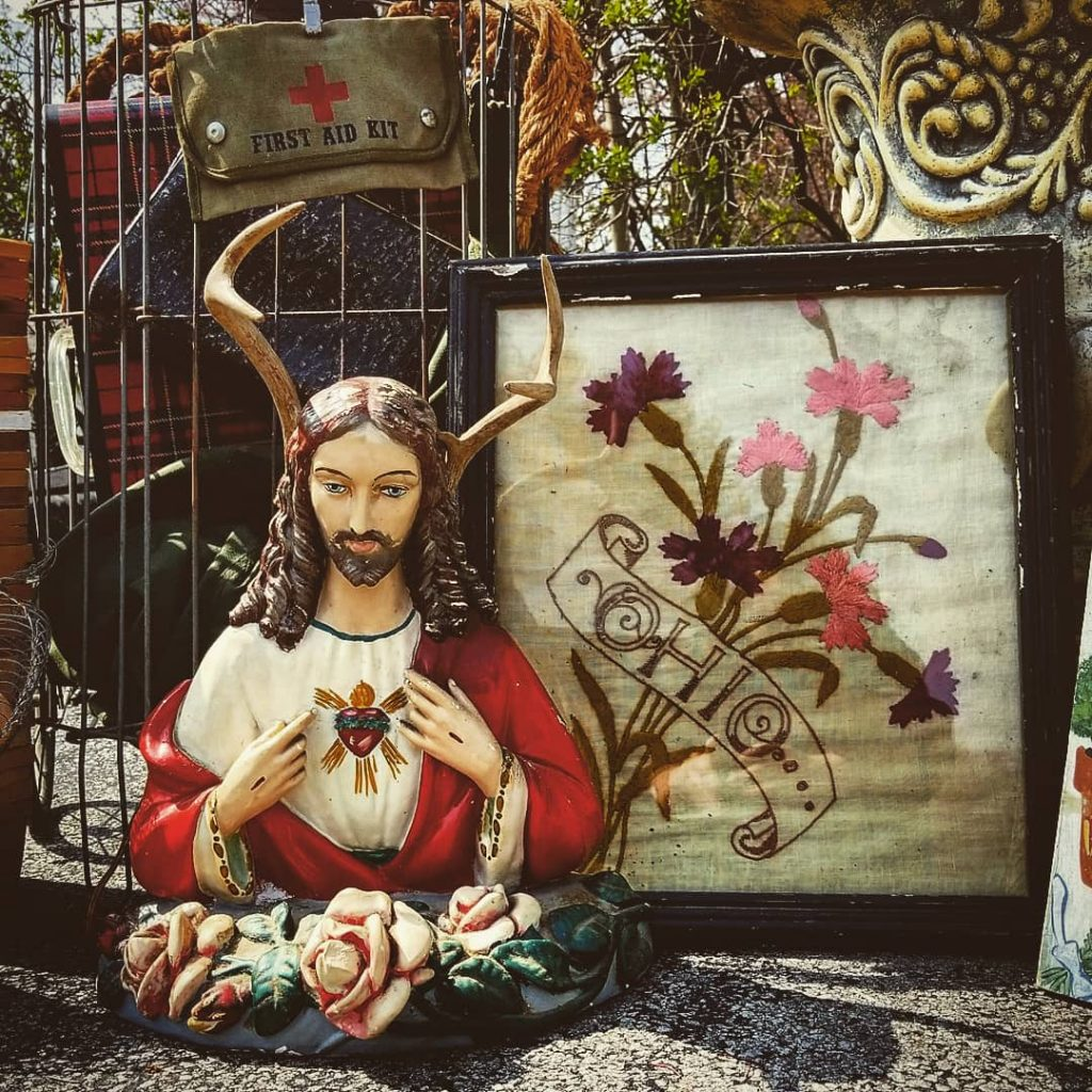 Jesus wearing antlers beside a needlepoint that says Ohio.